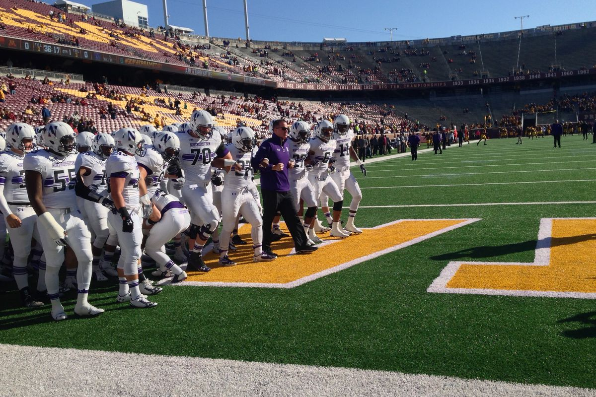 Pat Fitzgerald leads his players arm-in-arm onto the field before Northwestern's game against Minnesota on Oct. 11, 2014.