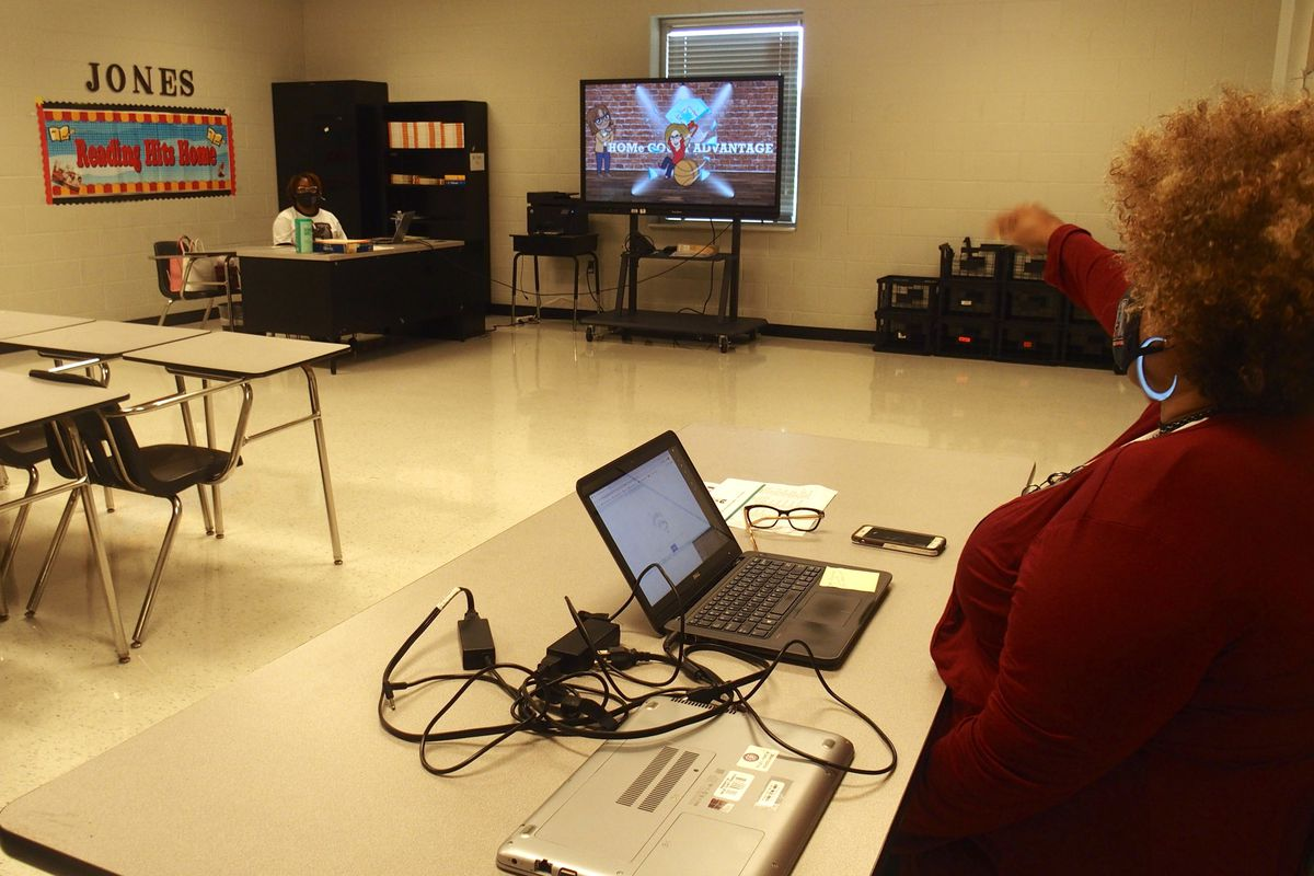 Teachers talk about an online class from across the room to social distance