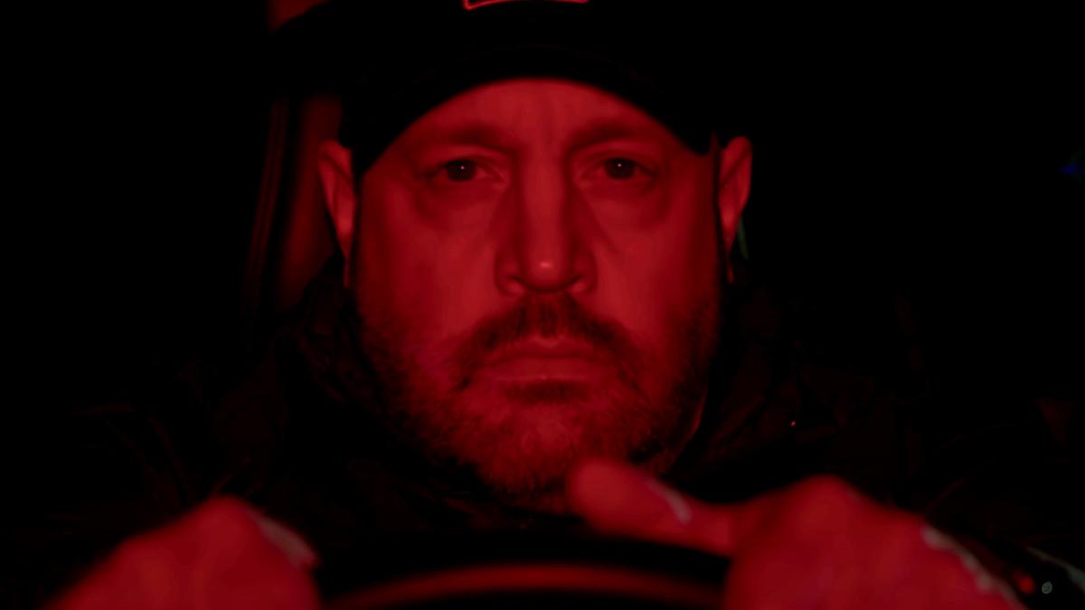 a man behind a steering wheel