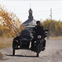 In this Sunday, Sept. 11, 2011 photo, a man rides a motorcycle in the village of Ust-Usa near the town of Usinsk, 1500 kilometers (930 miles) northeast of Moscow. Komi is one of Russia's largest and oldest oil provinces but ruptures in aging pipelines and leaks from decommissioned oil wells make oil spills in the region routine. (AP Photo/Dmitry Lovetsky)