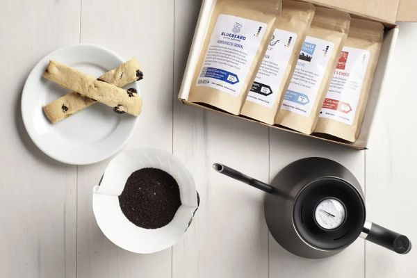 An overhead shot of a pour over electric kettle, coffee filter, plate of biscotti, and box of packaged coffee beans on a table