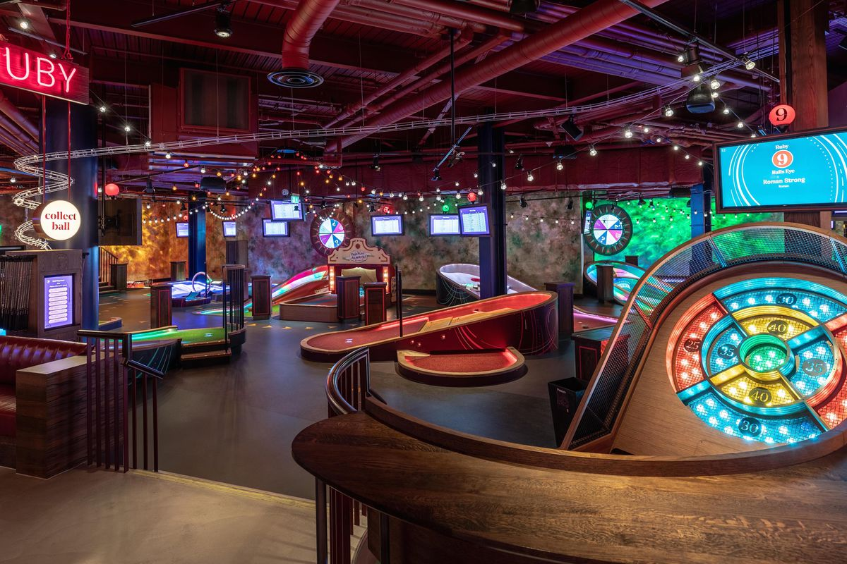 The interior view of an indoor golf course with many woods and screens.