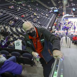 Garold Pope, guest services employee, sanitizes railings during a break in a preseason NBA game between the Utah Jazz and Phoenix Suns at the Vivint Smart Home Arena in Salt Lake City on Monday, Dec. 14, 2020. Attendees were also asked to wear masks and stay in their designated seats to adhere to social distancing.