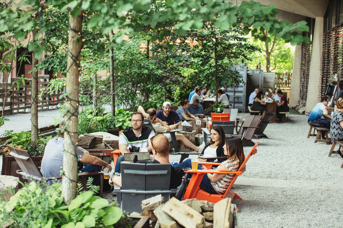 beer garden with trees, lights, people sitting in wood chairs