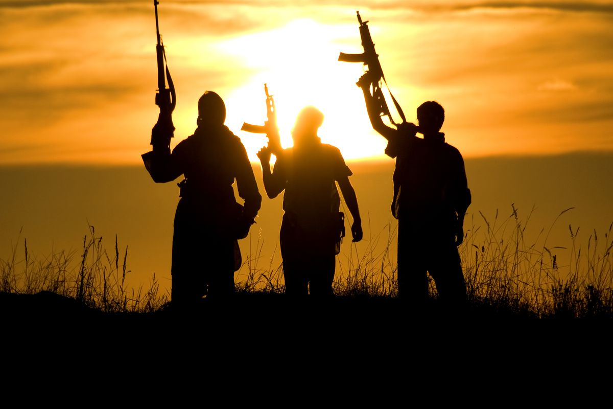 Silhouettes of several soldiers with rifles against a sunset.