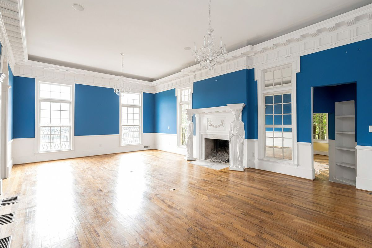 A huge blue living room with an ornate fireplace and five windows.