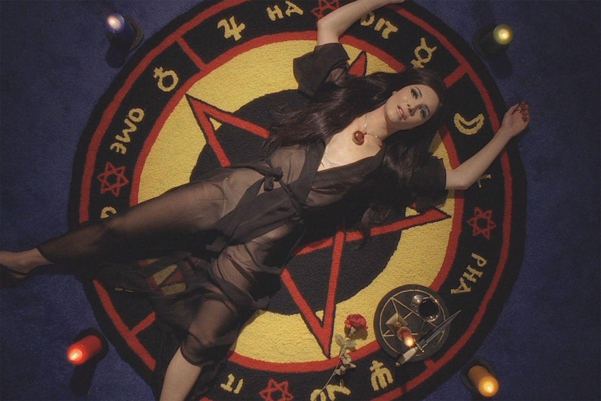 Elaine lays on a pentagram rug