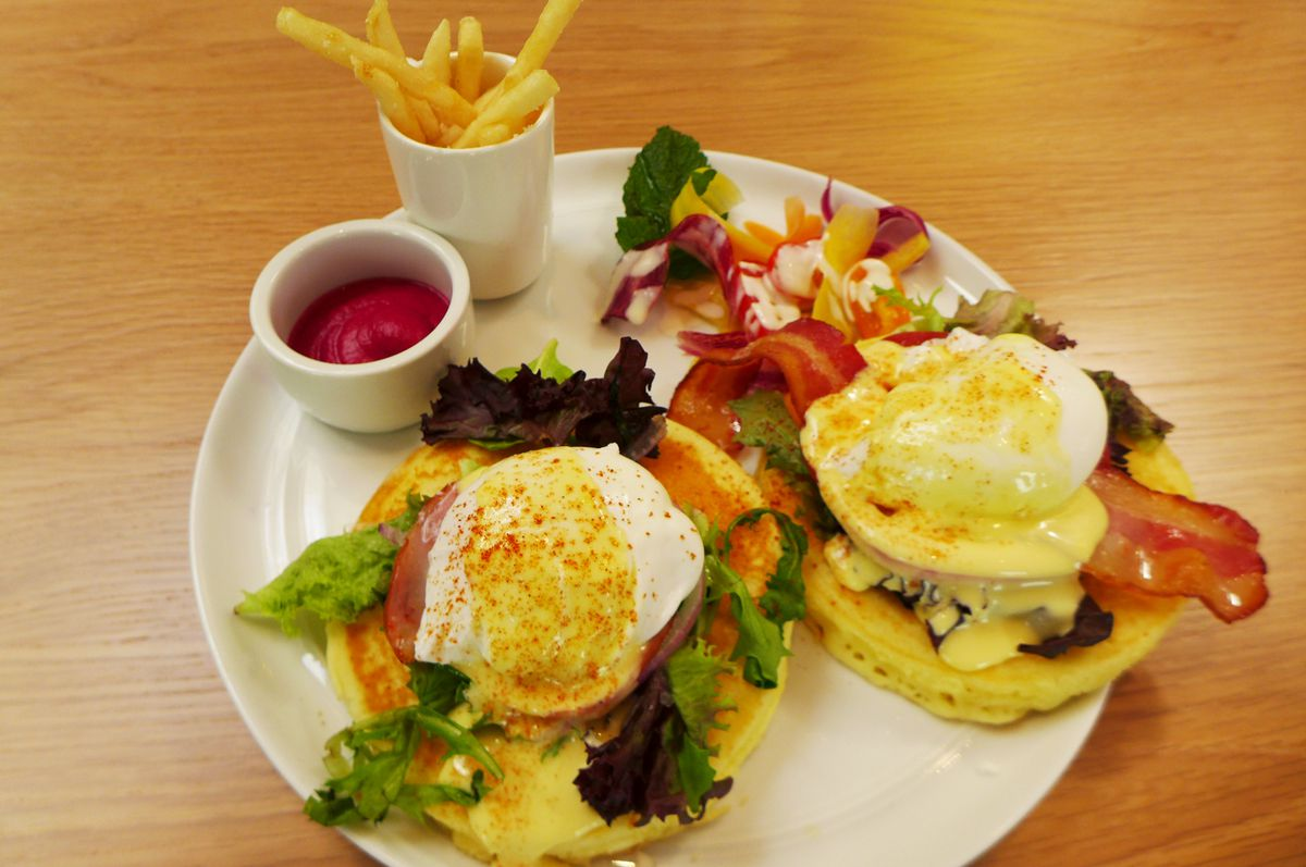 Plate contains french fries, beet ketchup, and a pair of pancakes with bacon and a poached egg on top...