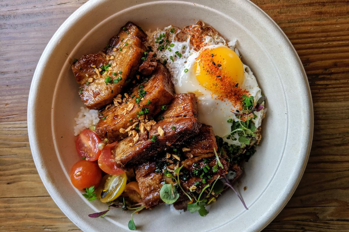 A bowl with rice, pork, fried egg, and vegetables at Spoon & Pork.