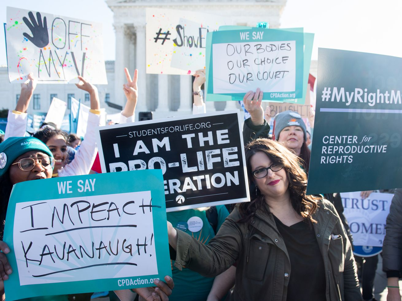"""Activists outside the Supreme Court holding signs with messages like """"Impeach Kavanaugh"""" and """"I am the pro-life generation."""""""