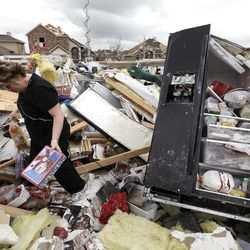 Ashley Quinton walks through the tornado damaged home of her friend Sherry Enochs in hopes of finding personal items that can be salvaged Wednesday, April 4, 2012, in Forney, Texas. Enochs was babysitting three children, all under the age of 3, that survived the storm with only minor bumps and scrapes.  (AP Photo/Tony Gutierrez)