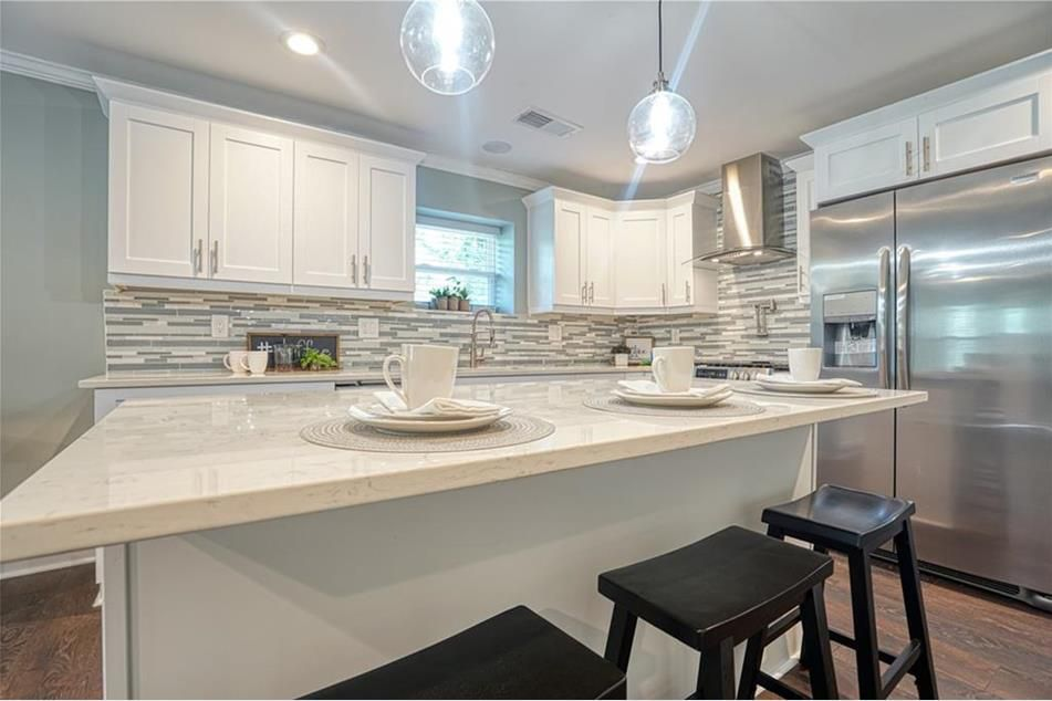 A kitchen with stainless appliances and white and black tiles.