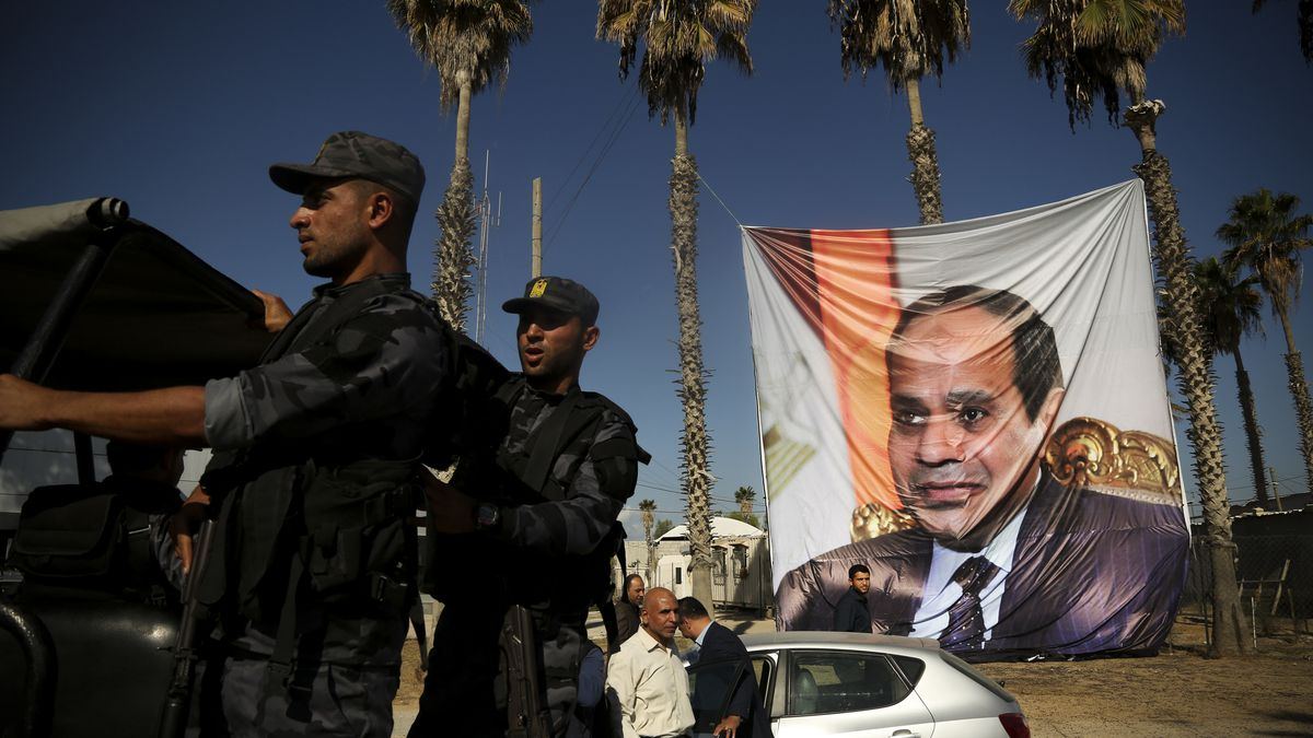 Palestinians hang a poster depicting Egypt's President Abdel Fattah al-Sisi at Rafah border crossing with Egypt, in the southern Gaza Strip November 1, 2017.