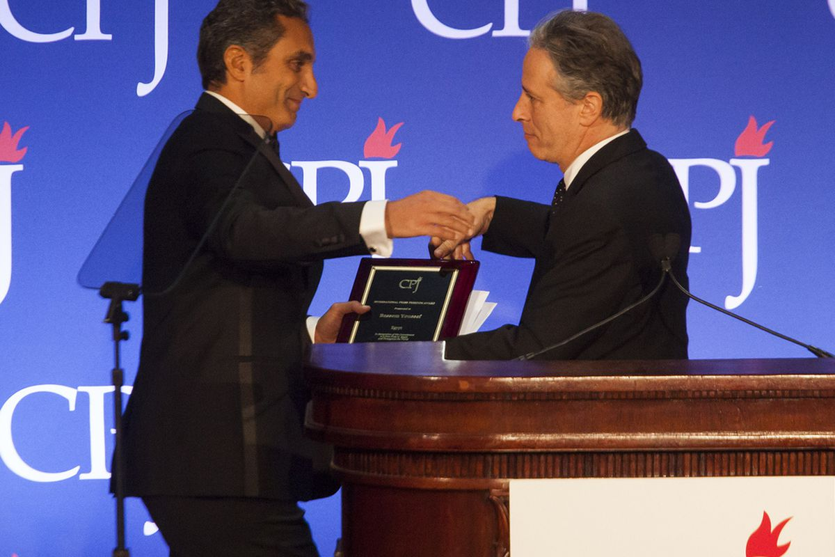 Bassem Youssef embraces Jon Stewart at a ceremony to accept an award from the US-based Committee to Protect Journalists a few months after cheering on Egypt's military coup and crackdown on Islamist protesters