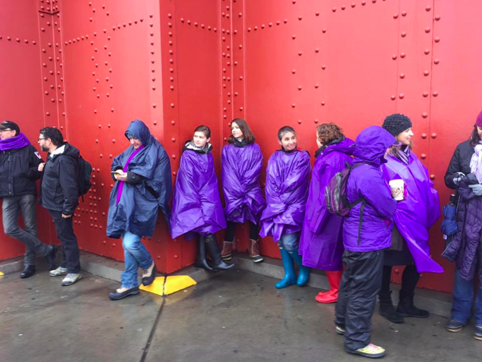 Protesters dressed in purple and standing on the bridge waiting to join hands