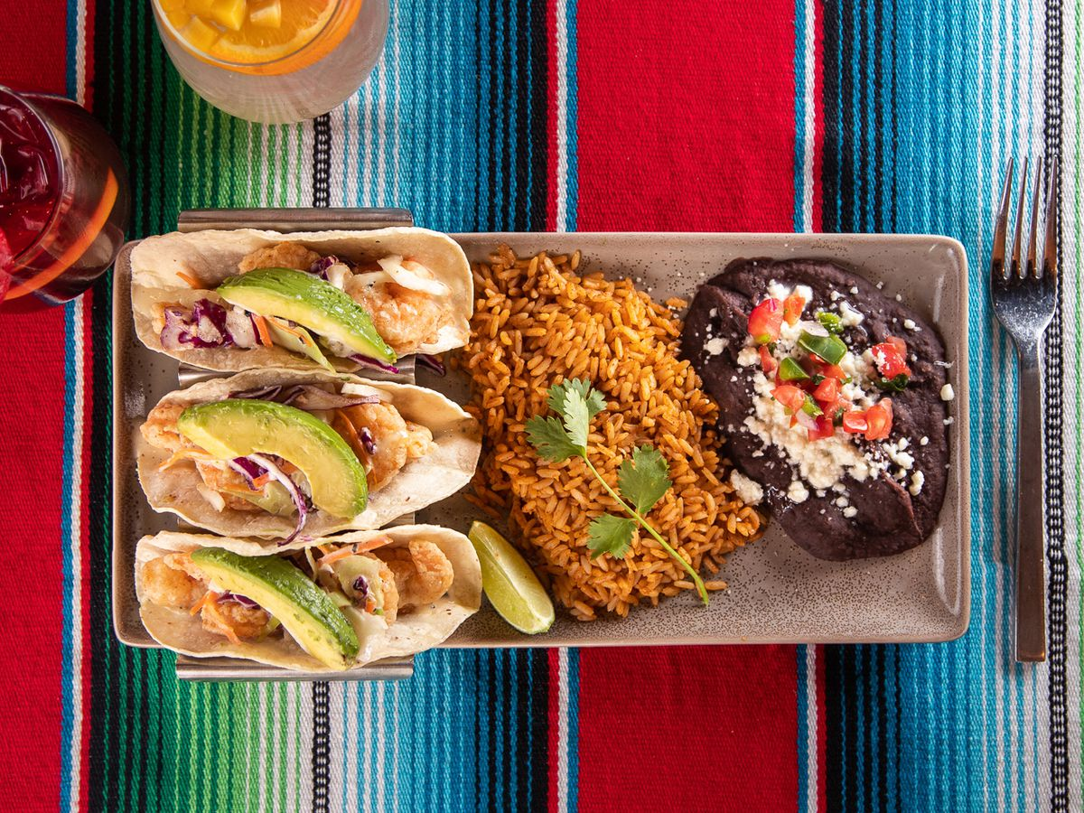 Tacos with rice and beans on a colorful tablecloth, with margaritas in the background, at Chayo Mexican Kitchen + Tequila bar.