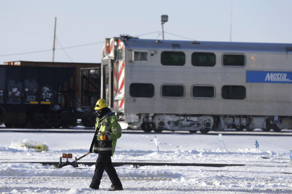 A silver commuter trains on the tracks as a worker clears snow.