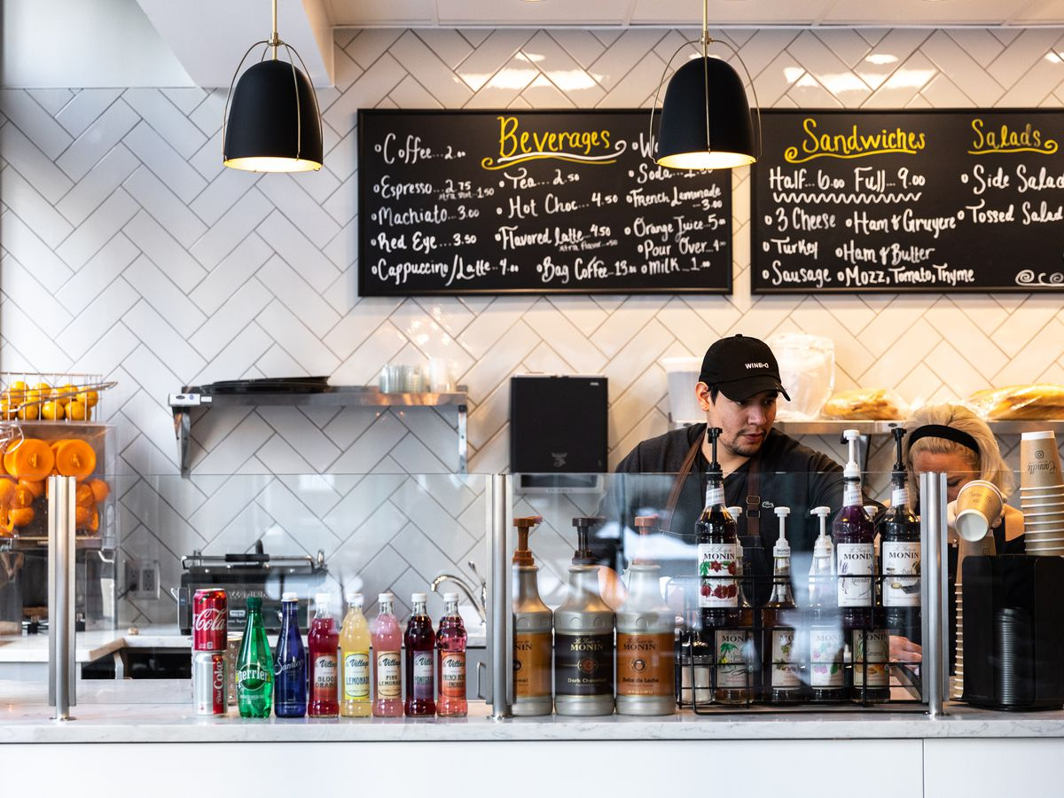 a barista in a black hat behind a white espresso counter with a glass window at cannelle