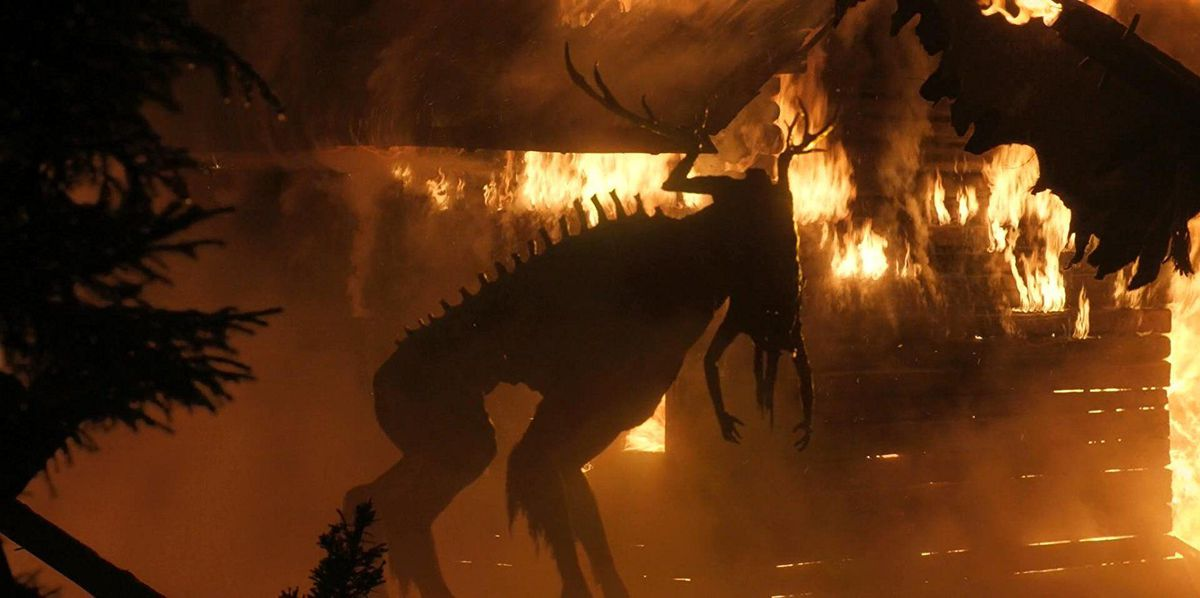 A elk-like monster composed of human body parts hunches in front of a burning cabin
