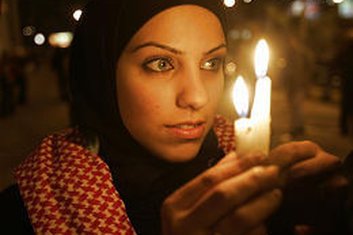 A Jordanian woman lights candles Saturday in front of an Amman hotel that was targeted by suicide bombers.