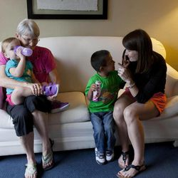 In this Thursday, Sept. 6, 2012 photo, Jessica Hooker, right, plays with her adopted son Daniel as Jessica's mom, Judy Russell holds granddaughter Ellyson, in Guatemala City. Daniel was 18 months old when the Tennessee couple Ryan and Jessica Hooker began the process to adopt him in Guatemala. They just got him at age 6. His is one of hundreds of adoption cases that were put in limbo five years ago, when the Guatemalan government declared a moratorium on international adoptions because of irregularities and fraud.