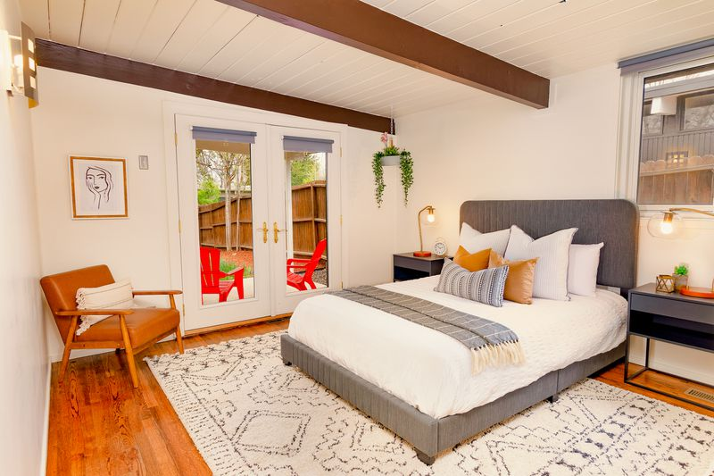 A gray bed sits on a gray and white rug in a bedroom with exposed beams.