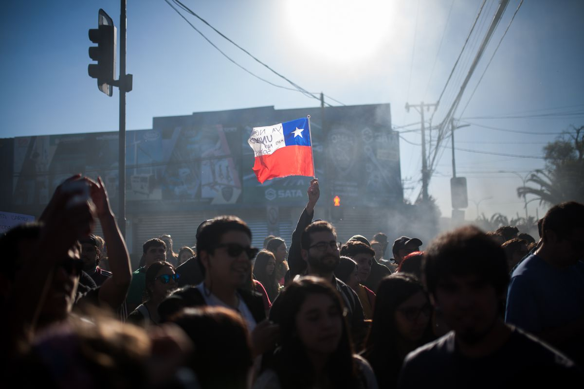 A demonstrator in a smoky outdoor crowd holds up a small Chilean flag.