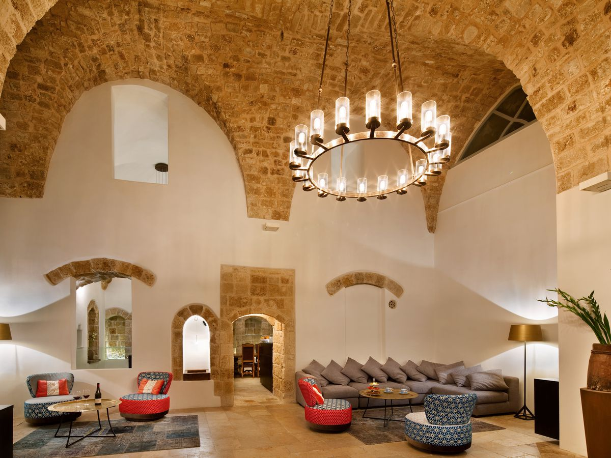 Inside a large hotel lounge with high vaulted, exposed brick ceilings, a large round chandelier, couches and chairs, and rooms visible through an open cut-out doorway and interior window