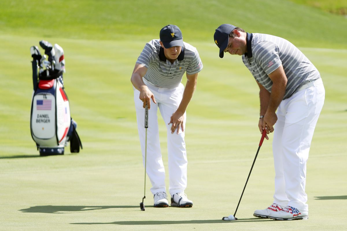 Patrick Reed putts and Jordan Spieth looks on