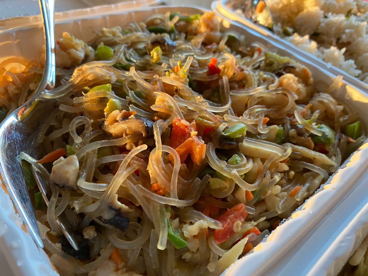 Takeout container of glass noodles tossed with shrimp, peppers, shiitake mushrooms, and water chestnuts