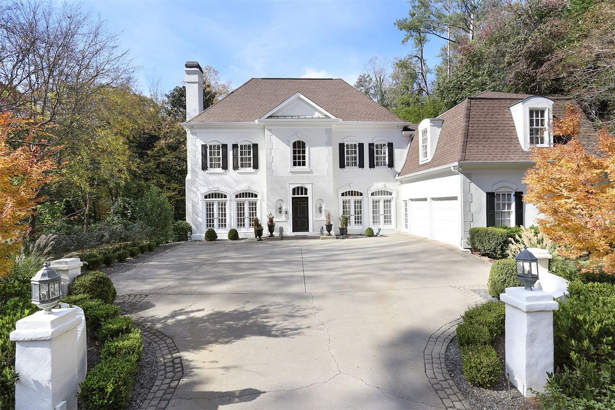 The white, two-story French Provincial home with four car garage to the right.