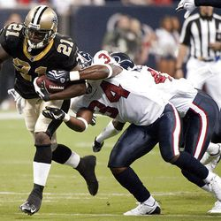 New Orleans Saints' Mike Bell (21) runs by Houston Texans' Dominique Barber (34) for a first down.
