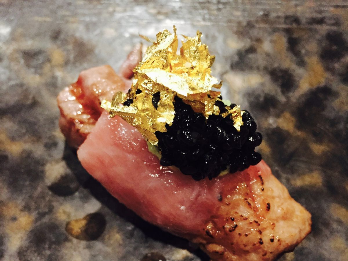 A piece of tuna placed on a marble counter. The fish is topped with gold flakes and black caviar.
