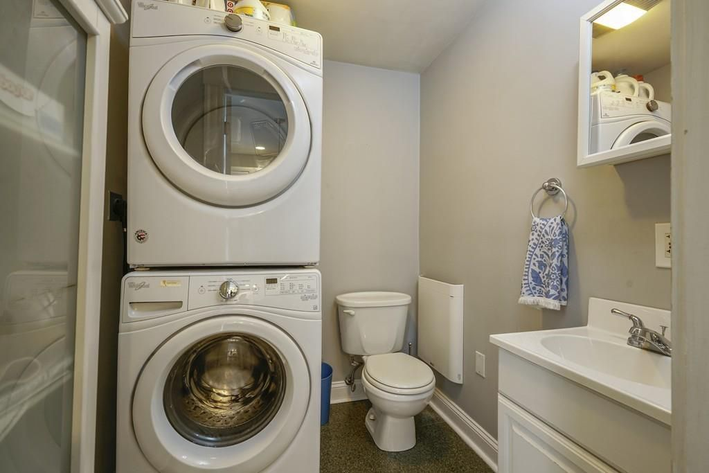 A half-bathroom with a washer-dryer stacked next to the toilet.