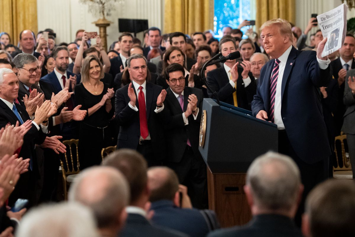 """Trump holds up a Washington Post front page that says """"Trump Acquitted"""" as notable Republicans including Vice President Mike Pence, AG Bill Barr, dozens of lawmakers, and members of his impeachment defense team applaud him."""