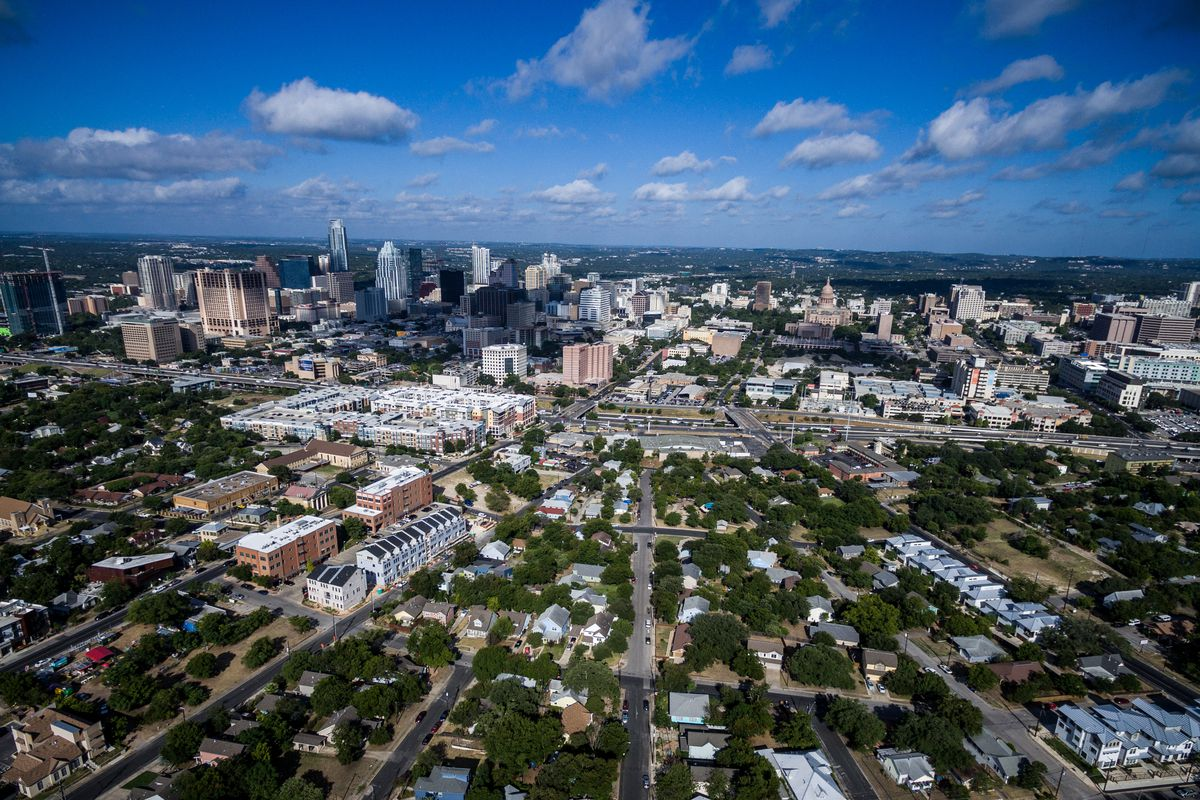 An aerial view of the city of Austin. There are neighborhood streets with houses and a more dense center with skyscrapers and larger buildings.