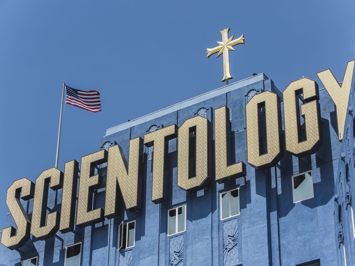 The exterior of the church of scientology building which is the former cedars of lebanon hospital in Los Angeles. The facade is blue and there is a large sign on the building that reads: scientology.
