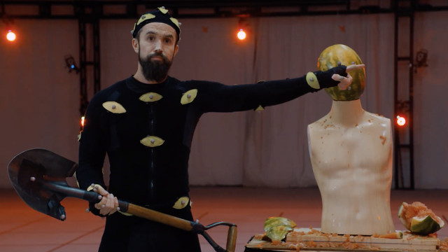 Rob McElhenney in a mocap suit, shovel in hand, pointing offscreen. in the background, a shirtless mannequin has a watermelon head