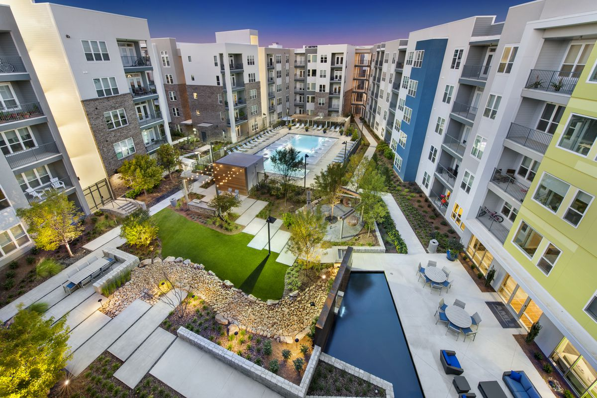 Courtyard with swimming pool surrounded by multi-story, colorful apartment buildings.