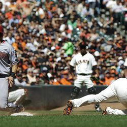 Arizona Diamondbacks' Paul Goldschmidt, left, slides safely at third base past San Francisco Giants third baseman Pablo Sandoval after a sacrifice fly ball from Chris Johnson during the sixth inning of a baseball game, Monday, Sept. 3, 2012, in San Francisco.