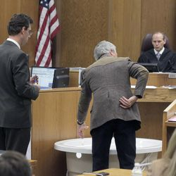 Ergonomics expert Brett Besser, center, testifies at Martin MacNeill murder trial in 4th District Court in Provo Thursday Nov. 7, 2013. He explains to defense lawyer Randy Spencer the stress to the lower back and difficulty in lifting a heavy weight from a bathtub. Judge Derek Pullan watches the demonstration.
