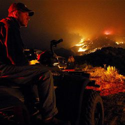 Vernile Prince watches the fire as it pushes closer to his home.  Crews started a back burn to halt the advance.