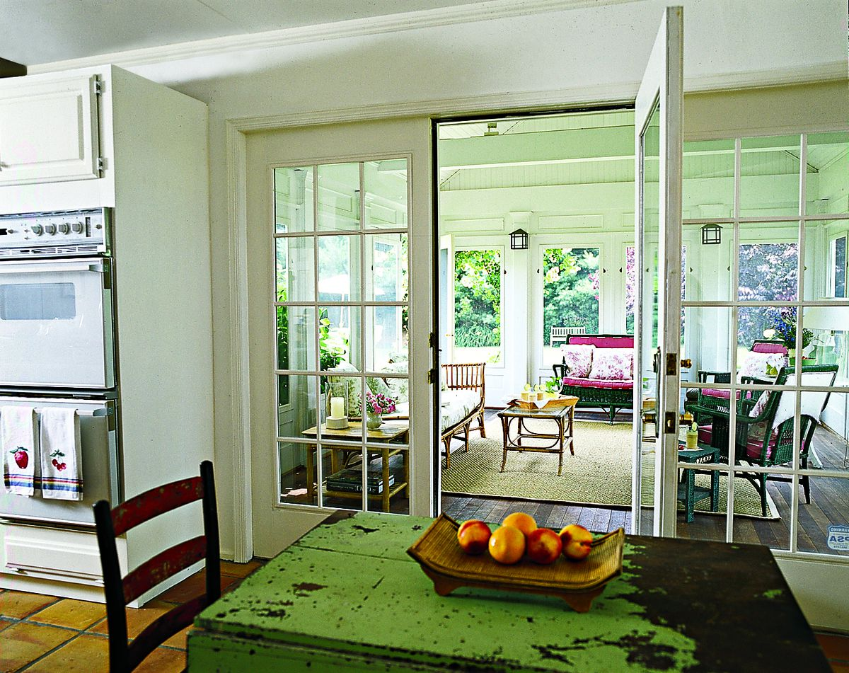 <p>The kitchen's French doors once led straight to the sun-filled backyard. The three-season addition creates a more gradual transition from house to garden to pool, leaving the interior cooler but still bright.</p>