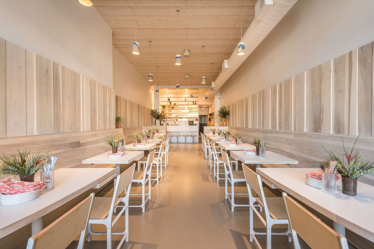A blonde wood and light white interior of a new restaurant bathed in California light.