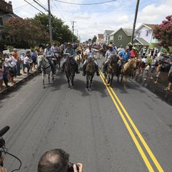 Volunteers with the Saltwater Cowboys walk wild ponies and foals through the streets of Chincoteague, Va., after the ponies swam from nearby Assateague Island during the 94-year-old swim tradition of Pony Penning on Wednesday, July 24, 2019. During the event, the horses navigate through the water for a couple hundred yards, and, after resting, are walked down the streets of town and eventually end up at a carnival where the foals are actioned.