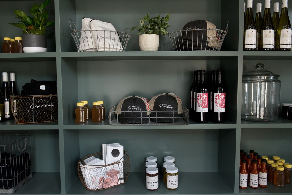 Three rows of shelves displaying various goods, including baseball caps and bottles of wine and sauces.