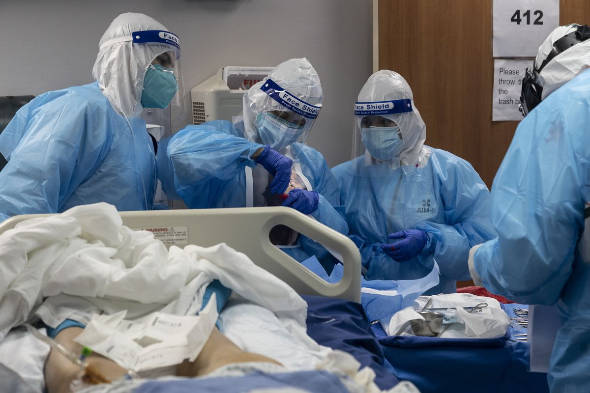 Four people encased in blue plastic, their heads in white hoods, clear face shields over their faces, and surgical masks over their mouths cluster over a patient in a bed. They appear to be working intently.