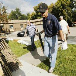 Paul Buckle of the Knights of Columbus and some LDS volunteers carry tables as they help Catholics set up for the Carmelite Fair at the monastery in Holladay Tuesday, Sept. 16, 2014.