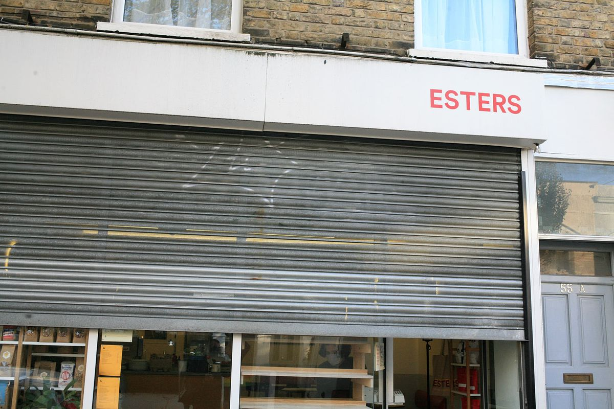 The frontage of Stoke Newington Cafe Esters, with a grey shutter rolled down halfway