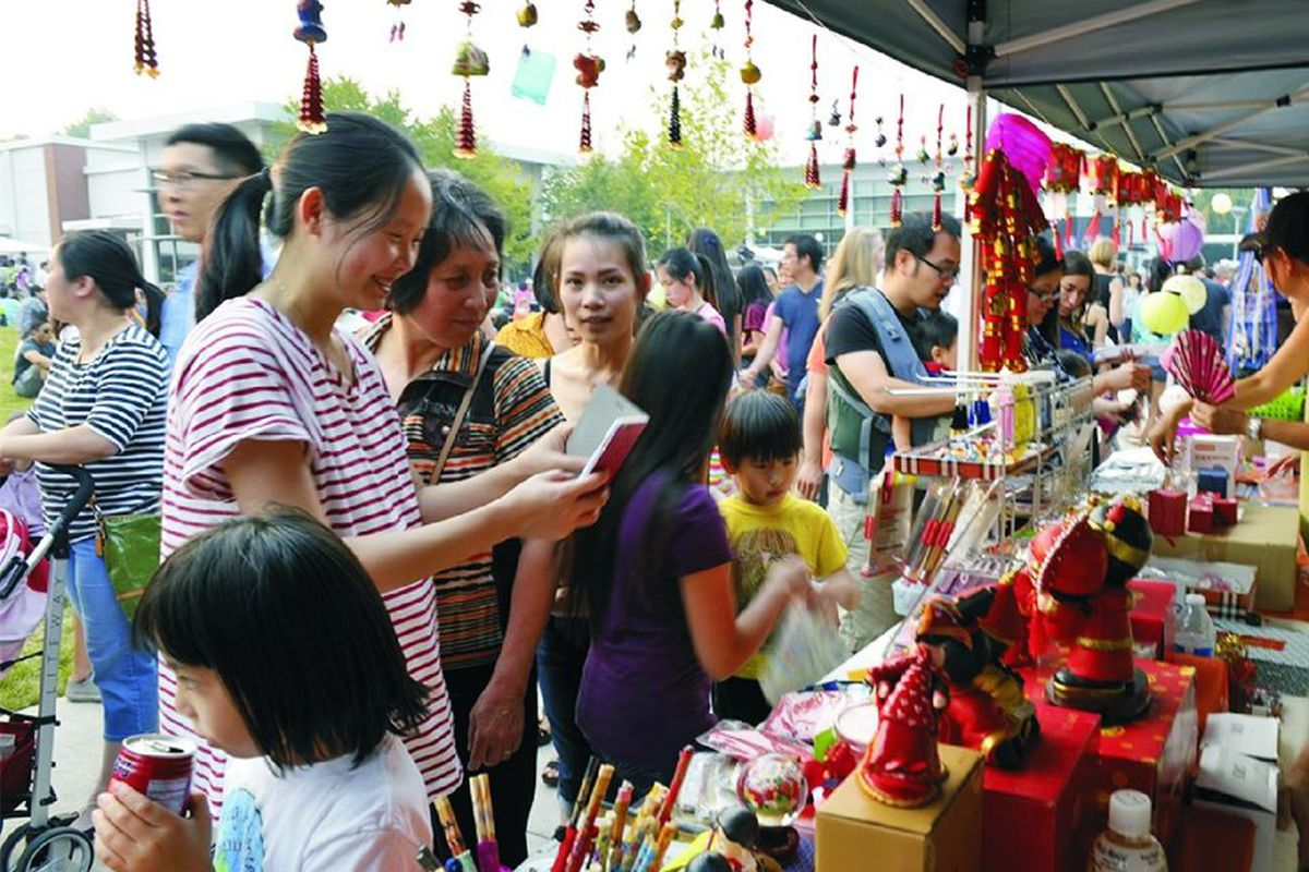 A crowded group look at stalls within the Jade International Night Market.